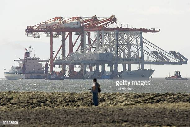 A photographer stands on the shore of the Burrard Inlet as three of the world's largest Super PostPanamax Cranes float into harbour April 27 2005 in...