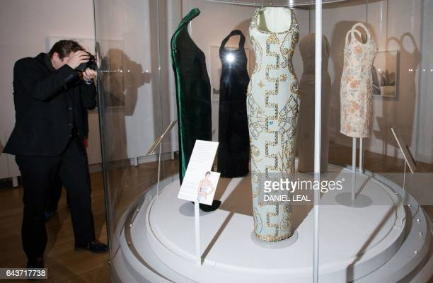 TOPSHOT A photographer takes a photograph of a display of dresses including on by the designer Gianni Versace and worn by Britain's Diana Princess of...