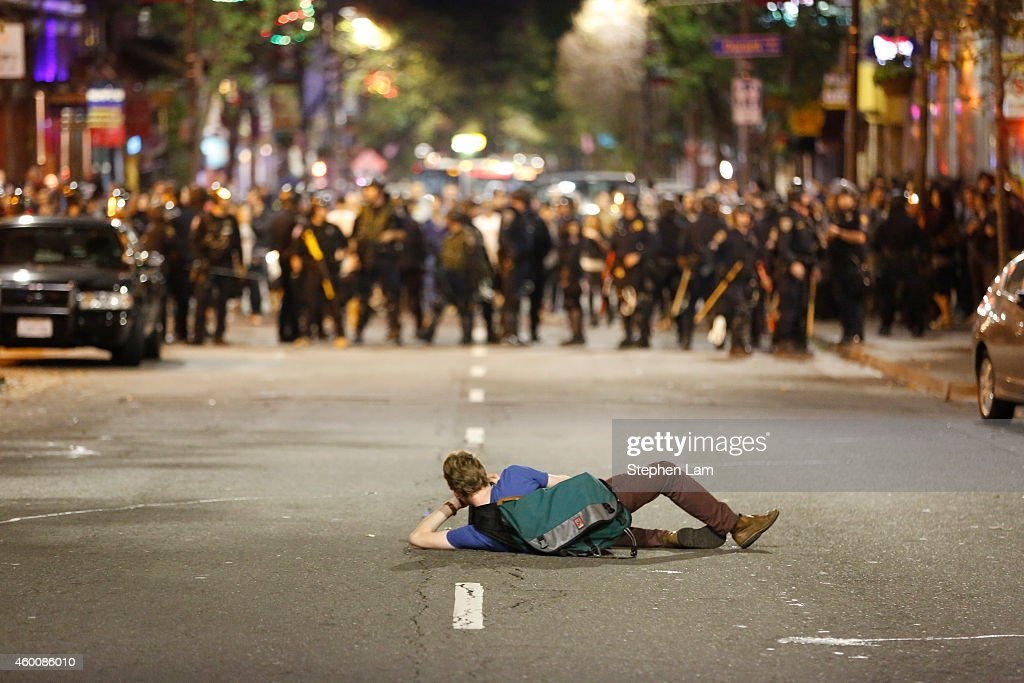A photographer takes a photograph of a police line on Telegraph Ave on the fourth night of demonstrations over recent grand jury decisions in...