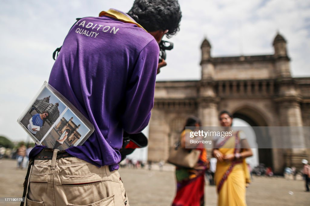 A photographer takes a photograph of two woman near the Gateway of India memorial building in Mumbai, India, on Wednesday, Aug. 21, 2013. The prospect of an indecisive 2014 election in India is eroding confidence among global investors that the government can stop the rupees worst drop in more than two decades. Photographer: Dhiraj Singh/Bloomberg via Getty Images