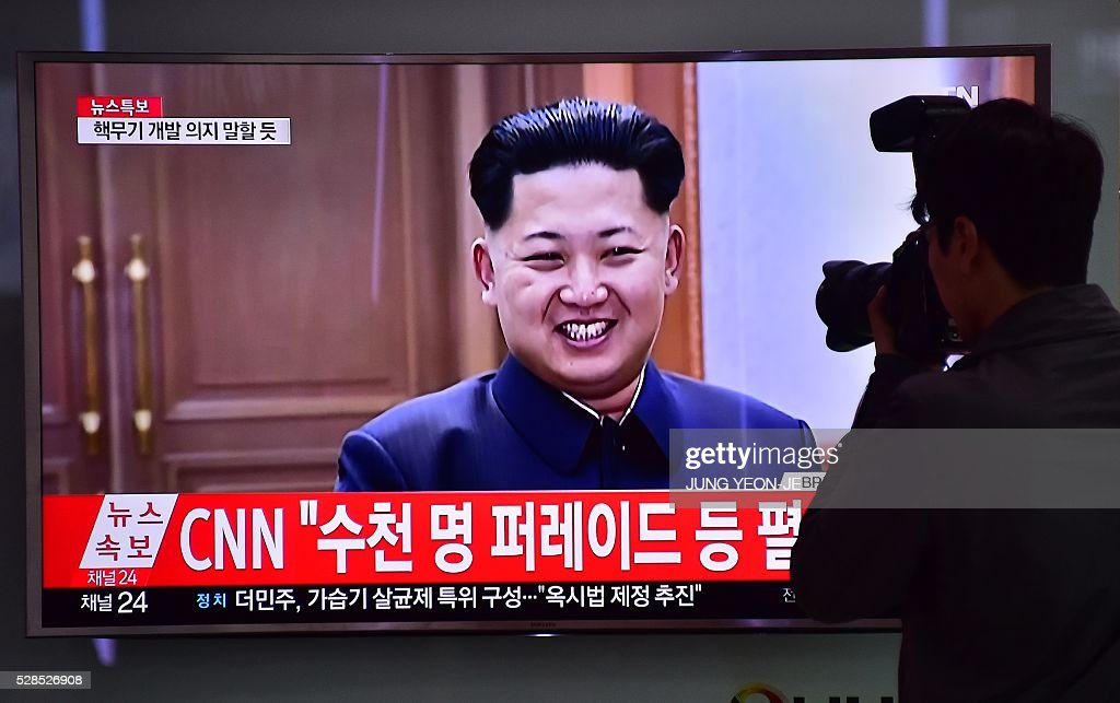 A photographer takes a picture of a television screen showing file footage of North Korean leader Kim Jong-Un, at a railway station in Seoul on May 6, 2016. North Korea raised the curtain on May 6 on its biggest political show for a generation, aimed at cementing the absolute rule of leader Kim Jong-Un and shadowed by the possibility of an imminent nuclear test. / AFP / JUNG
