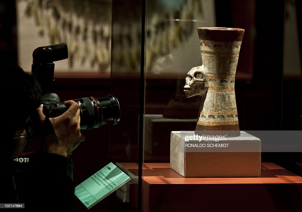 A photographer takes a picture of a vessel during a presentation for the press of the exhibition 'Moctezuma II' at the Templo Mayor museum, in Mexico City, on June 16, 2010. AFP PHOTO/Ronaldo Schemidt