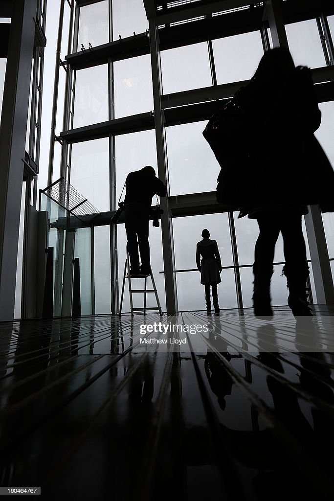 A photographer takes a picture of a woman looking out over London from the View from the Shard on it's opening morning on February 1, 2013 in London, England. Level 72 is the highest viewing gallery in The View from The Shard, and the highest vantage point in Western Europe.