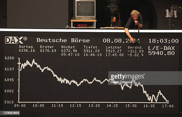 A photographer takes a picture of the German DAX Index board showing the day's performance of the Frankfurt Stock Exchange on the first day following...