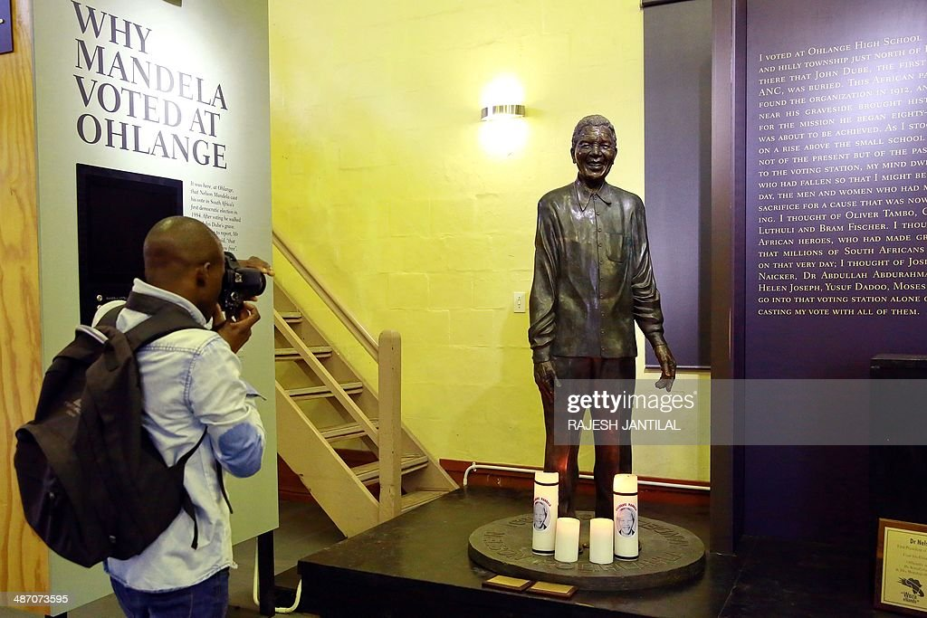 A photographer takes a picture of the statue of former South African President Nelson Mandela at the Inanda Museum, north of Durban, on April 27, 2014 at the Ohlanga High School where Nelson Mandela cast his vote on April 27, 1994 in the first democratic elections of the post-Apartheid era. Freedom Day celebrations mark the 20th anniversary of the country's first democratic elections in the post-Apartheid era.