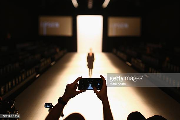 A photographer takes a picture on their mobile phone as a model walks the runway during rehearsal ahead of The Innovators Fashion Design Studio show...