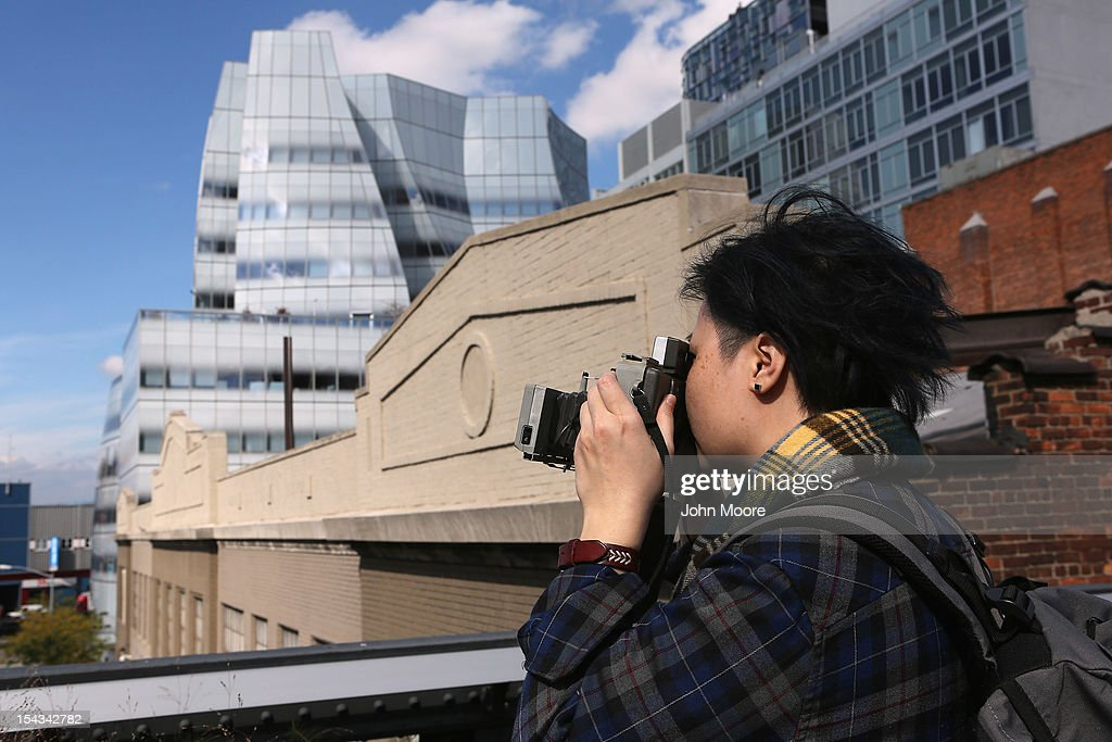 A photographer takes a Polaroid image near the office of Newsweek Magazine in the Frank Gehry-designed IAC Building (L), on October 18, 2012 in New York City. Tina Brown, editor-in-chief of The Newsweek Daily Beast Co, announced today that the 80-year-old news magazine will publish its final print edition on December 31 and shift to an all-digital format in early 2013. Staff layoffs are expected.