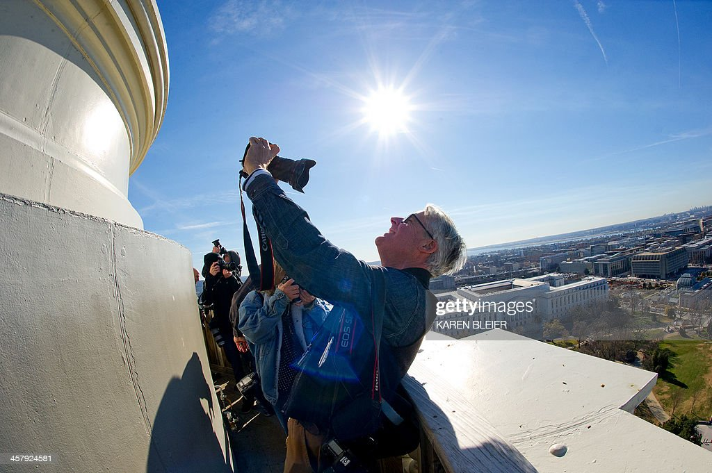 A photographer takes a selfie from the top of the US Capitol dome during a tour of the dome December 19, 2013 in Washington, DC. The Dome has not undergone a complete restoration since 1959-1960 and due to age and weather is now plagued by more than 1,000 cracks and deficiencies. The Architect of the Capitol began in November, a multi-year project to repair these deficiencies, restoring the Dome to its original, inspiring splendor. AFP PHOTO / Karen BLEIER