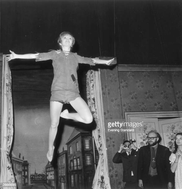A photographer takes a snap of Hayley Mills daughter of Sir John Mills and Mary Hayley Bell 'flying through the air' during a rehearsal of Peter Pan...