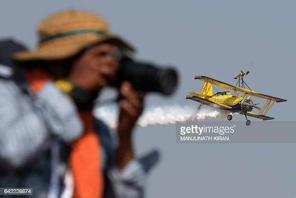 A photographer takes images of an aerial display of aircraft on the fourth day of the 11th edition of 'Aero India' a biennial international aerospace...