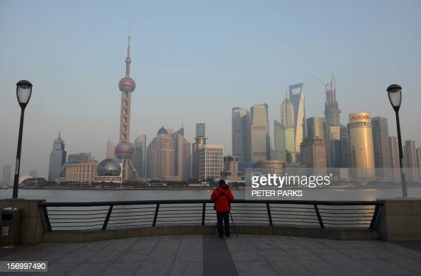 A photographer takes photos of the financial district of Pudong from the Bund in Shanghai on November 27 2012 Chinese shares closed at their lowest...