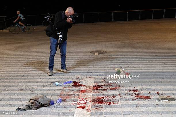 A photographer takes pictures as he arrives at the scene of a stabbing attack on March 8 2016 in the neighbourhood of Jaffa in the Israeli city of...