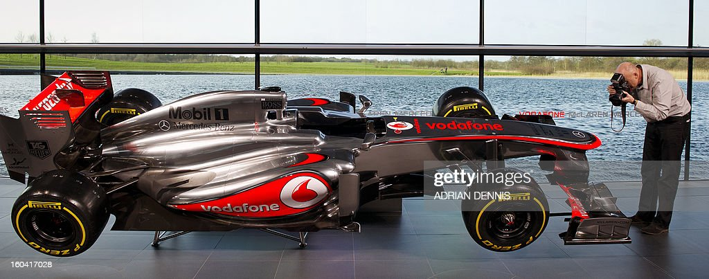 A photographer takes pictures as the new McLaren Mercedes MP4-28 F1 racing car for the 2013 season is unveiled at the McLaren Technology Centre in Woking, southern England, on January 31, 2013. Mexican driver Sergio Checo Perez joins Britain's Jenson Button for the 2013 season following the departure of Britain's Lewis Hamilton.