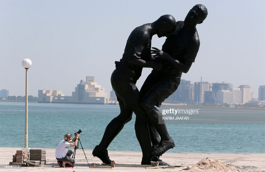 A photographer takes pictures of a bronze sculpture by French Algerian born artist Adel Abdessemed during its installation on October 4, 2013 on the Corniche in Doha after it was bought by the Qatar Museums Authority. The statue, titled 'Coup de Tete' immortalizes the 'headbutt' given by the French former football champion Zinedine Zidane to Italian player Marco Materazzi during the World Cup final in 2006.