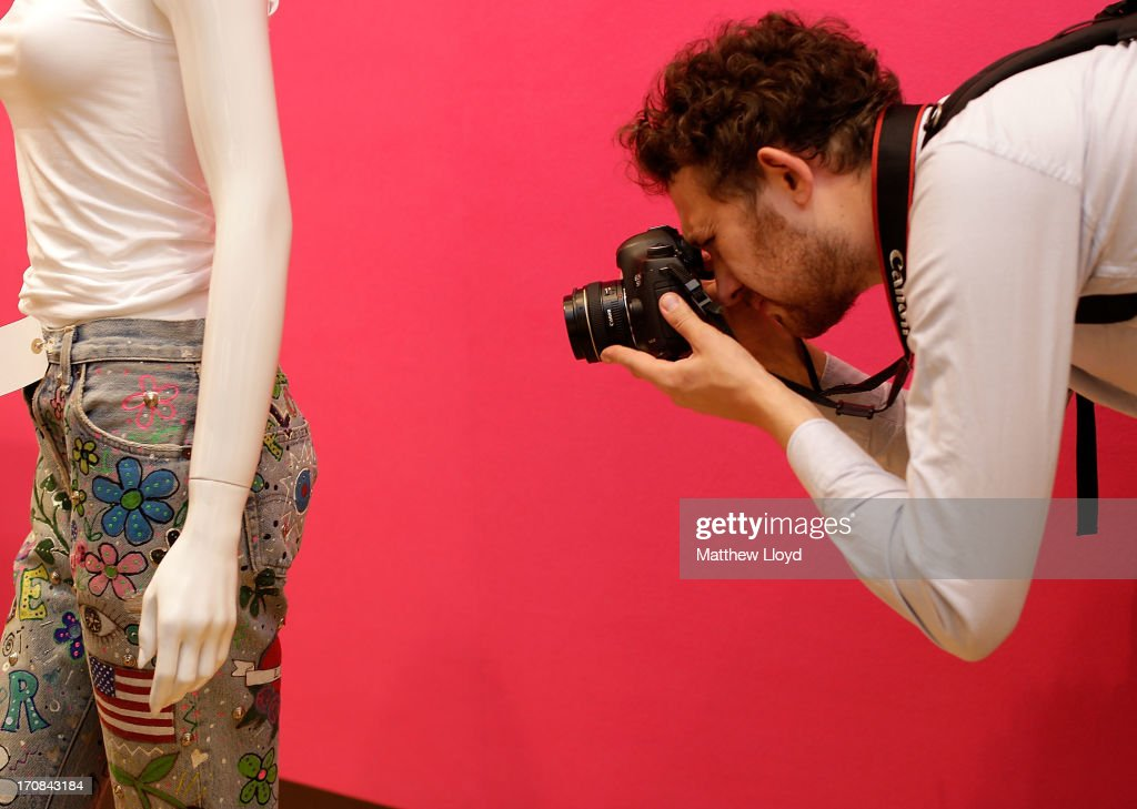 A photographer takes pictures of a pair of trousers, worn by Madonna in a magazine cover photoshoot, for sale at Christie's South Kensington on June 19, 2013 in London, England. The item is part of an auction entitled 'Pop Culture' featuring memorabilia charting the history of cinema, pop and rock and roll.