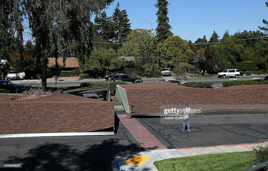 A photographer takes pictures of collapsed carports following a 6.0 earthquake on August 24, 2014 in Napa, California. A 6.0 earthquake rocked the San Francisco Bay Area shortly after 3:00 am on Sunday morning causing damage to buildings and sending at least 70 people to a hospital with non-life threatening injuries.