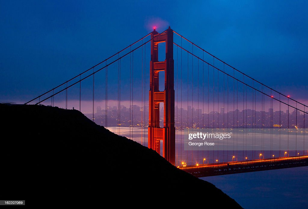 A photographer takes pictures of the Golden Gate Bridge as it is aglow in lights just before sunrise on February 13, 2013, in San Francisco, California. Some 13.6 million international travelers visit the State each year generating nearly $100 billion in revenue and creating approximately 900,000 jobs in the arts, entertainment, recreation, food service and accomodations sectors.