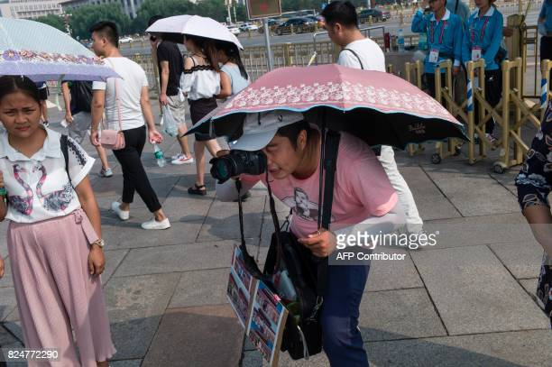 A photographer takes pictures of tourists at Tiananmen Square in Beijing on July 31 on the eve of the 90th founding anniversary of the People's...