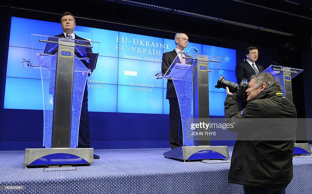 A photographer takes pictures while Ukrainian President Viktor Yanukovych (L), European Union President Belgian Herman Van Rompuy C) and European Commission President Jose Manuel give a press conference after an EU-Ukraine Summit at the EU Headquarters in Brussels on February 25, 2013. Viktor Yanukovych arrived in Brussels for a summit seen as 'a defining moment' in a long-delayed bid to seal a political and trade pact with the EU anchoring the ex-Soviet state closer to the West.