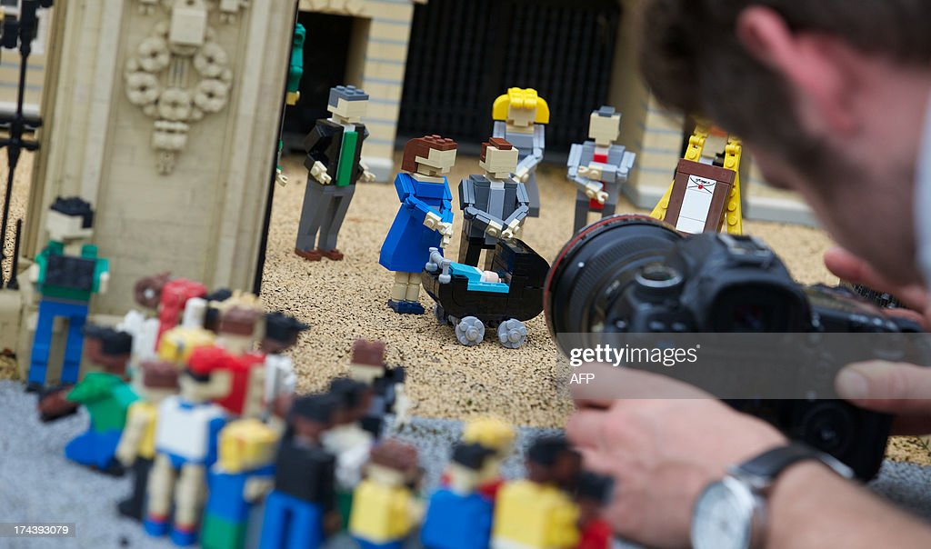 A photographer takes ppictures of Lego models of Prince William, the Duke of Cambridge and his wife Catherine, The Duchess of Cambridge along with a pram containing a model of their newborn baby boy George Alexander Louis are postitioned outside a 36000 Lego-brick model of Buckingham Palace at Legoland in Windsor on July 25, 2013. Britain's press gave their seal of approval to Prince William and his wife Kate's decision to name their newborn baby boy George Alexander Louis, saying it had 'kingly authority'.