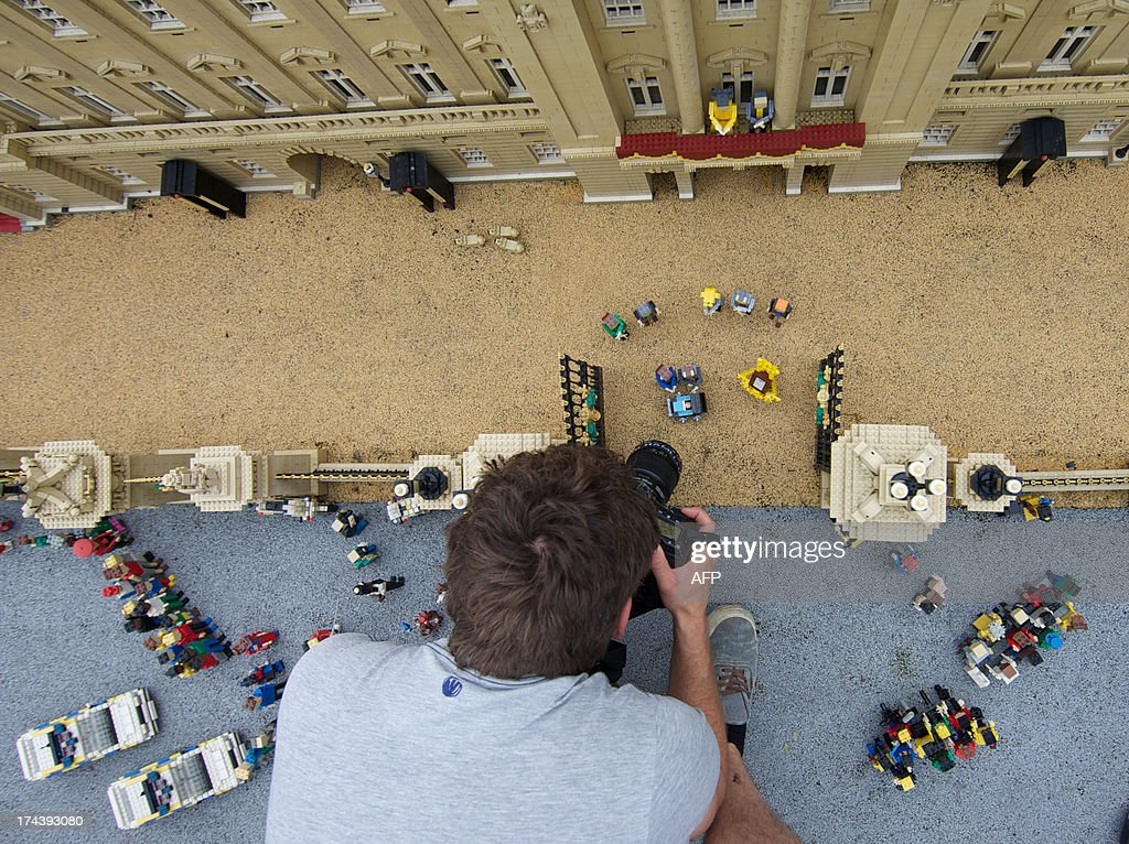 A photographer takes ppictures of Lego models of Prince William, the Duke of Cambridge and his wife Catherine, The Duchess of Cambridge along with a pram containing a model of their newborn baby boy George Alexander Louis are postitioned outside a 36000 Lego-brick model of Buckingham Palace at Legoland in Windsor on July 25, 2013. Britain's press gave their seal of approval to Prince William and his wife Kate's decision to name their newborn baby boy George Alexander Louis, saying it had 'kingly authority'. AFP PHOTO / ANDREW COWIE