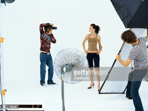 Photographer taking a photograph of a young woman in a studio : Stock Photo