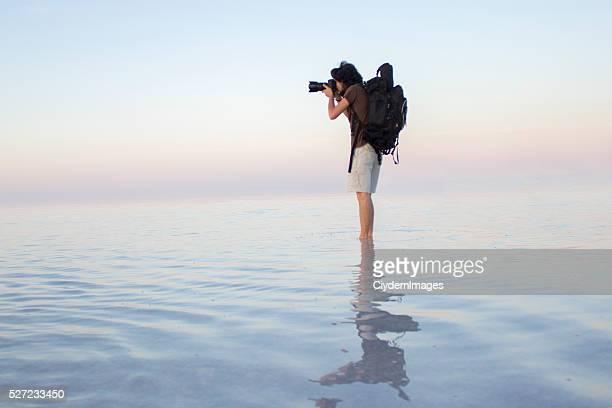 Photographer taking photo on water