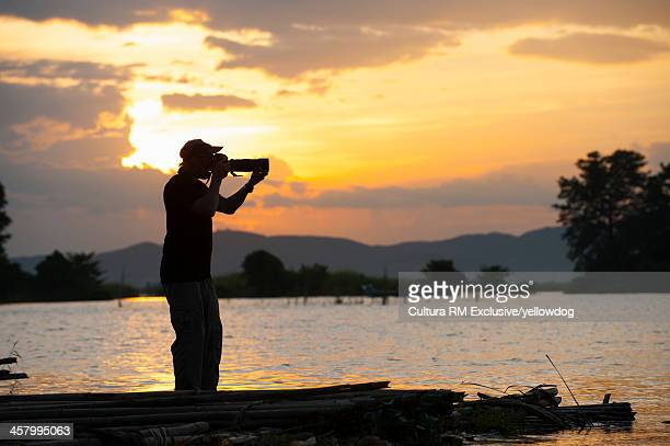Photographer taking photograph at sunset, Mandalay, Burma