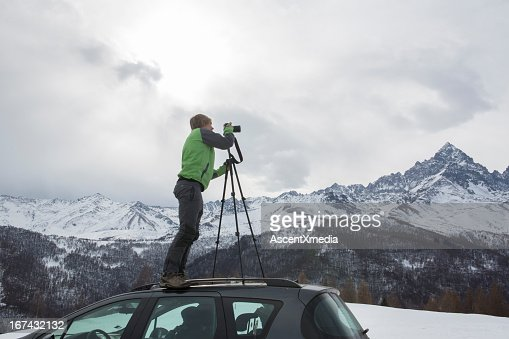 Photographer taking picture from top of car : Stock Photo
