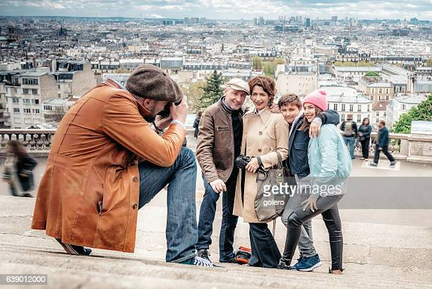 photographer taking picture of family on monmartre stairs in Paris