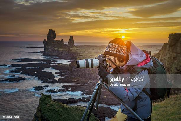 Photographer taking pictures at sunset, Iceland