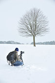 A photographer taking pictures of a bare tree in a snowcovered field in winter Hungerford January 15 2010