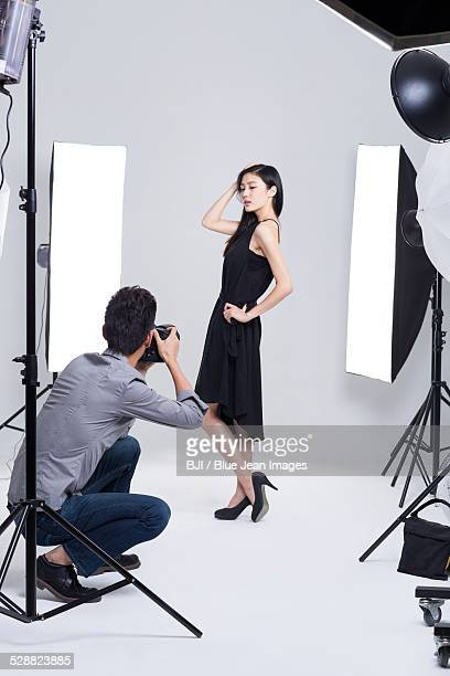 Photographer taking pictures of female model in studio