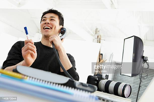 Photographer talking on phone at desk