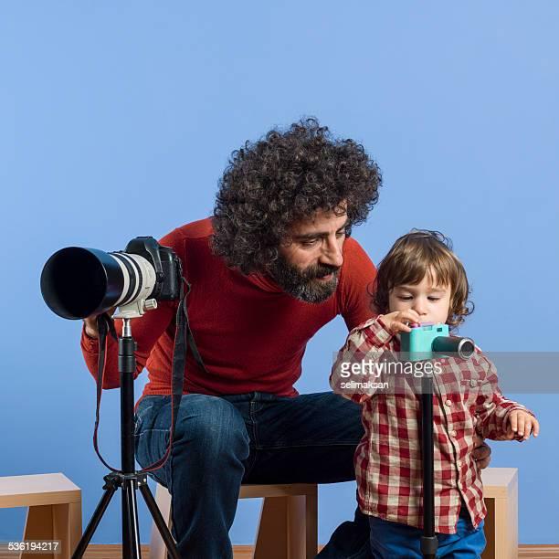 Fotografin zeigt seinen Sohn wie man die Kamera