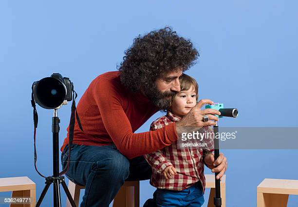 Photographer teaching his son how to use camera