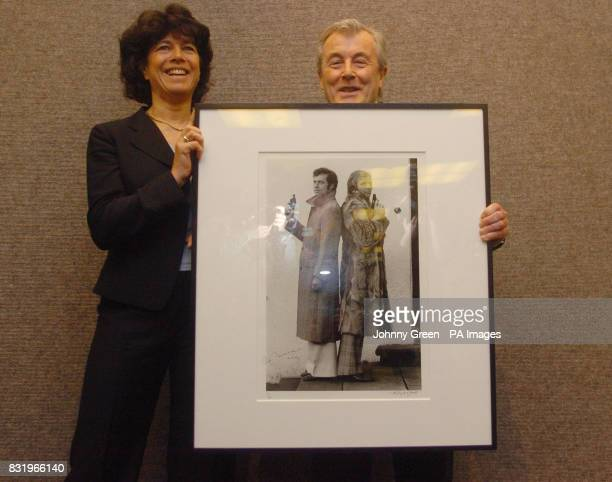 Photographer Terry O'Neill holds an iconic photograph taken by him of footballers Bobby Moore and Franz Beckenbauer with the widow of Moore Stephanie...