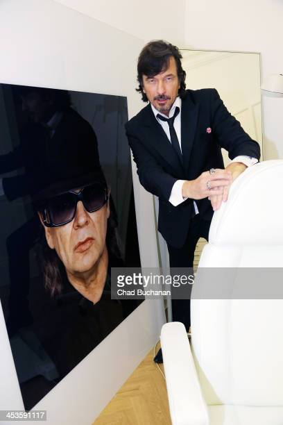 Photographer Tom Lemke poses next to one of his pictures at the Center of Aesthetics photo exhibition on December 4 2013 in Berlin Germany