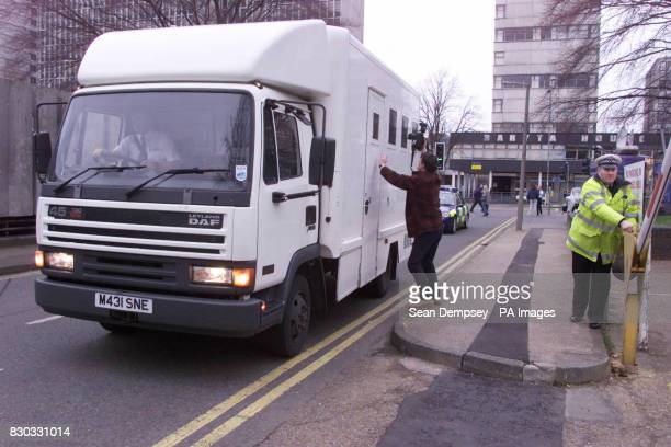 A photographer tries to obtain an image through a security vehicle window as the thirteen suspected hijackers arrive at Southend magistrates court...