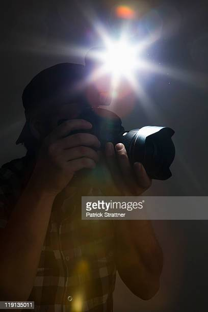 A photographer using a camera and flash