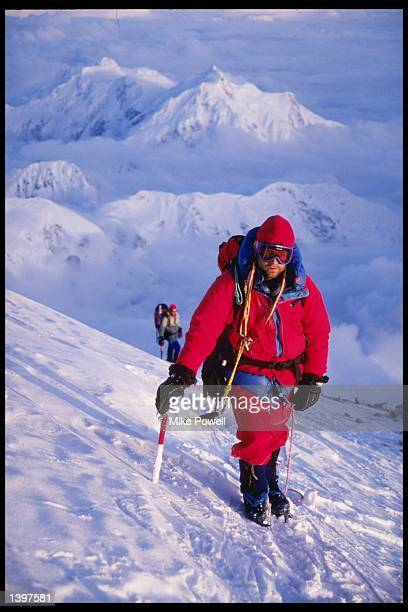 A photographer views a climber at Denali at the top of the West Rib reaching l9300 feet on Mount McKinley Alaska