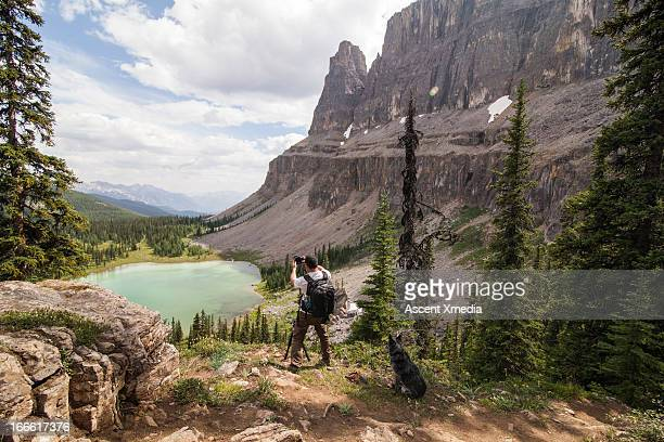 Photographer w dog compose picture above mtn lake