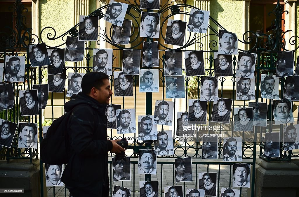 A photographer walks past photos of killed journalists stuck on the fence of the Veracruz state representation office during a journalists protest in Mexico City on February 11, 2016. Mexican journalist Anabel Flores Salazar's funeral took place Wednesday after she was found killed at a road after being kidnapped Monday in Veracruz state, one of the most dangerous for journalists. AFP PHOTO/RONALDO SCHEMIDT / AFP / RONALDO SCHEMIDT