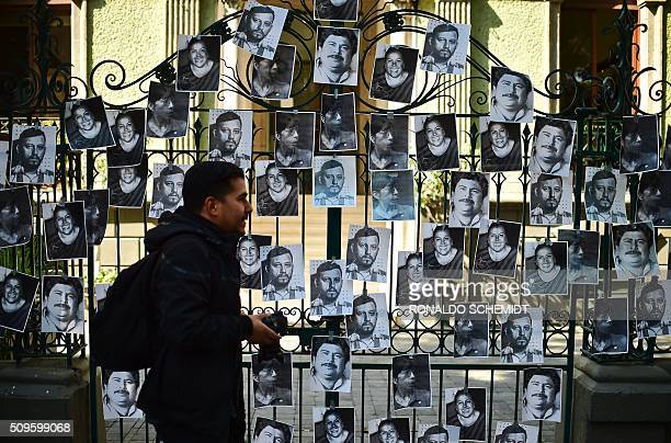 A photographer walks past photos of killed journalists stuck on the fence of the Veracruz state representation office during a journalists protest in...