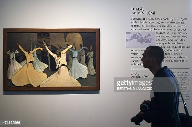 A photographer walks past 'The whirling Turkish dervishes' by Andre Sureda part of the 'Lieux Saints partages' exhibition held at the at the Museum...