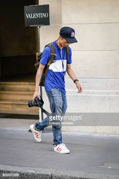 A photographer wears a cap a blue and white polo shirt blue denim jeans white sneakers outside the Valentino show during Paris Fashion Week Menswear...