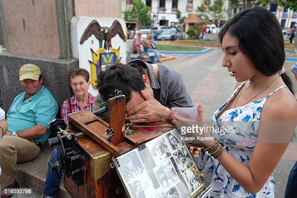 A photographer with a vintage view camera busy taking a snap photo for the visitors while a young Colombian woman looks at a print presently made...