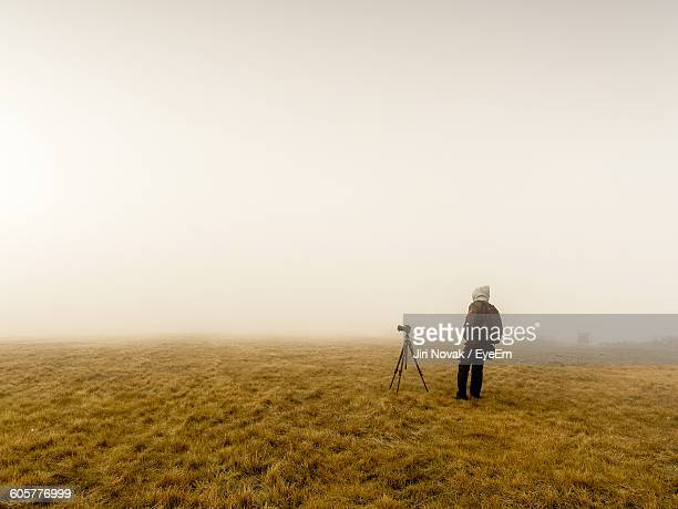 Photographer With Tripod On Field In Foggy Weather