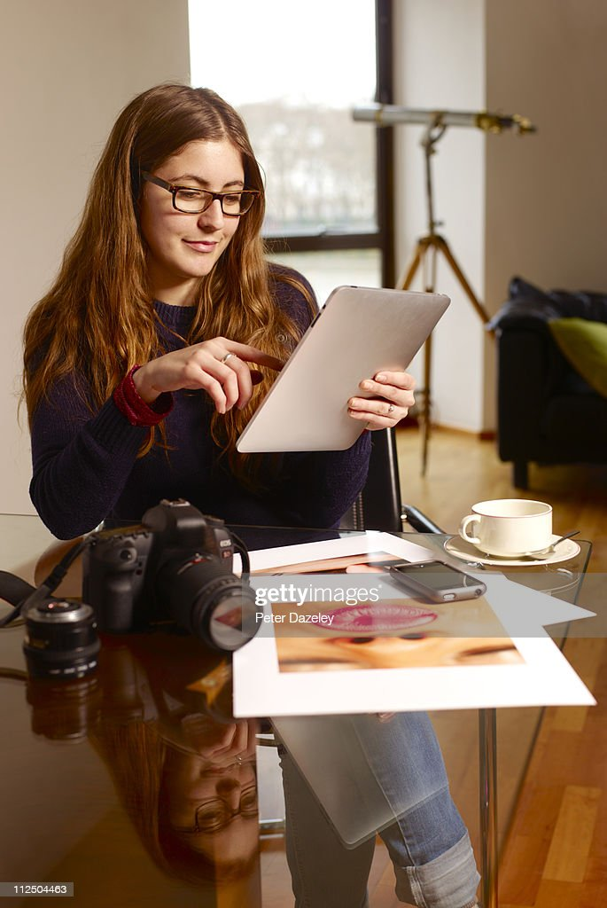Photographer working on digital tablet : Stock Photo