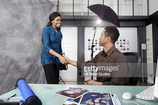 Photographer working with client in studio : Stock Photo